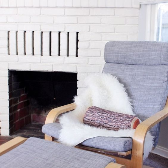 Grey Ikea Poang Chair With Faux Sheepskin and a Log Pillow